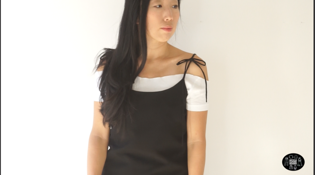 Front view of the black DIY silk slip dress with a white off the shoulder top underneath.