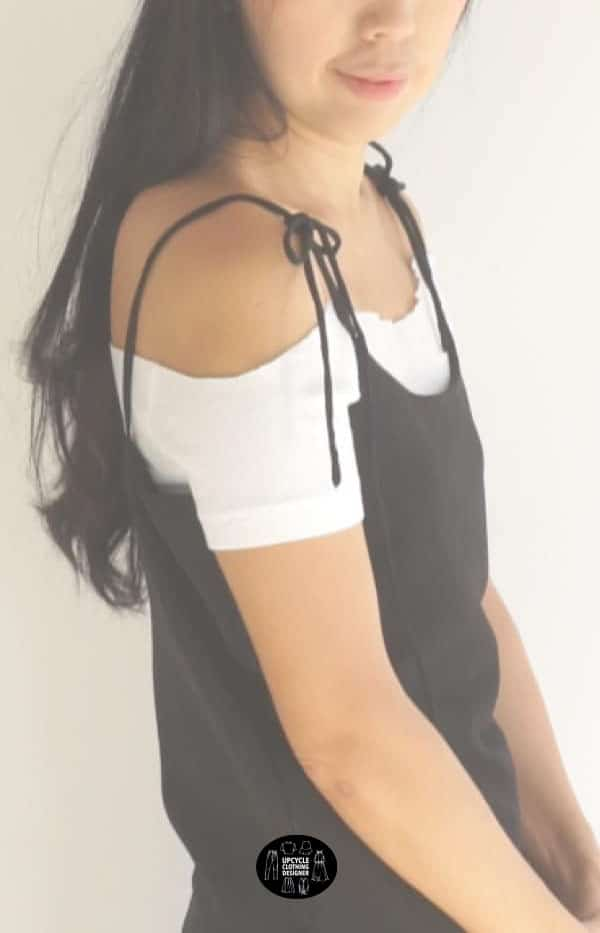 Sideview of the black DIY silk slip dress with a white off the shoulder top underneath.