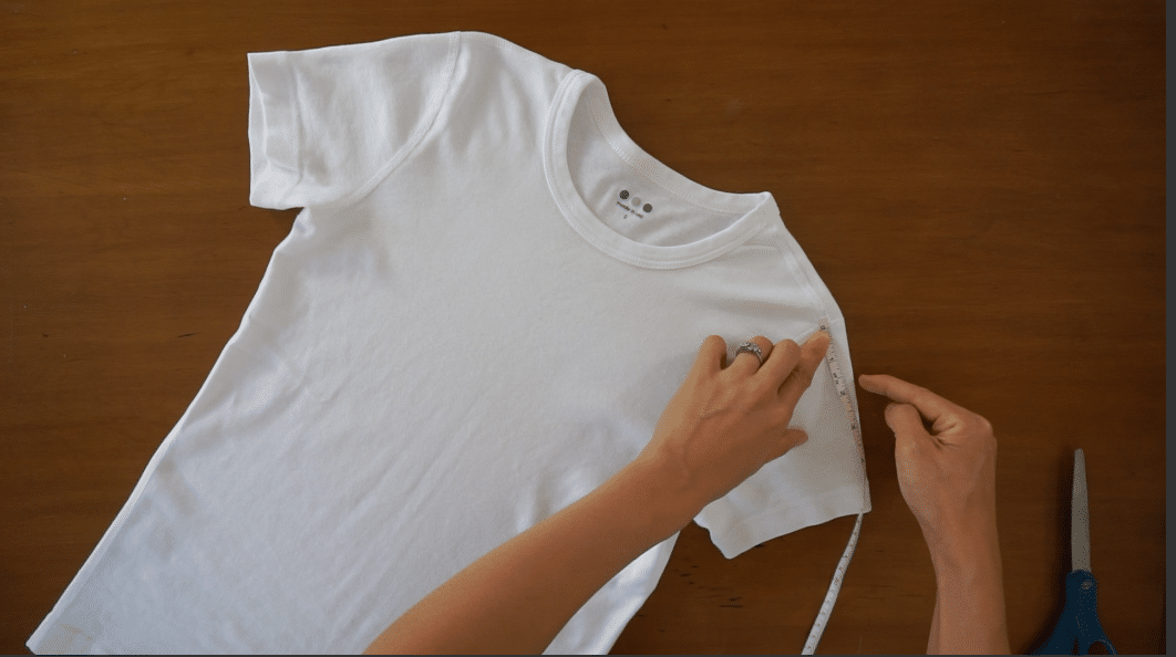 measure from the shoulder seam to determine where to start cutting on both sides of the t-shirt.