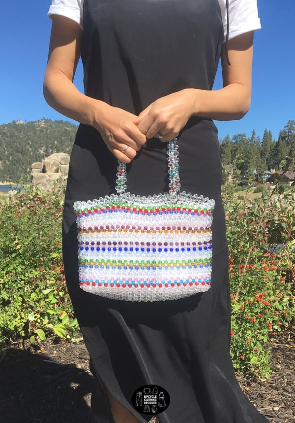 Beaded bag with handles. The striped pattern interchanges between colorful and clear beads.