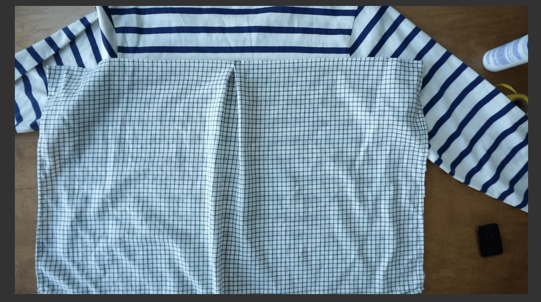 Lay the back piece of the woven shirt over the back piece of the knit top.
