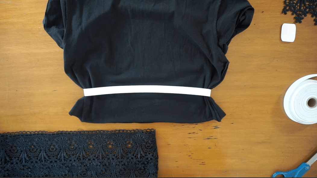 Make a large loop using the elastic band and secure the ends together. Slide the elastic band over the bottom of the cut shirt.