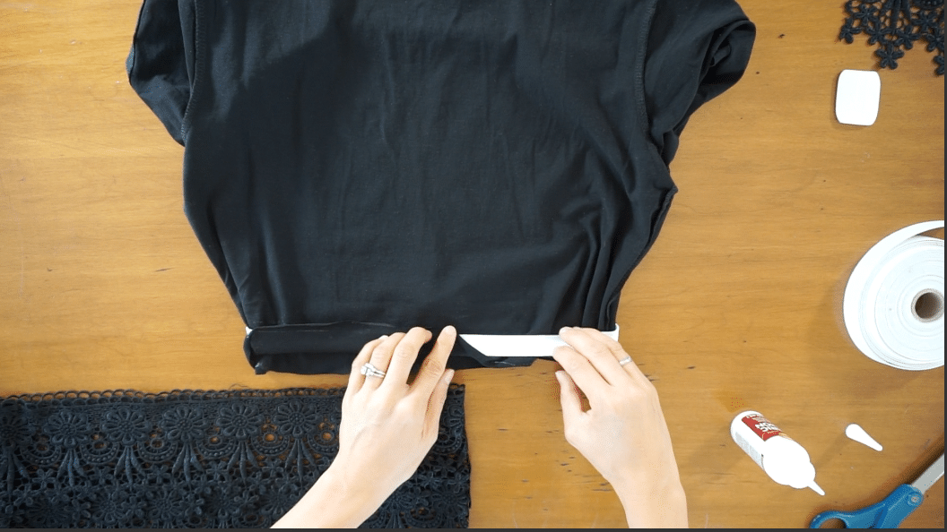 Fold the shirt bottom over the elastic band to cover with fabric. Secure with fabric glue.