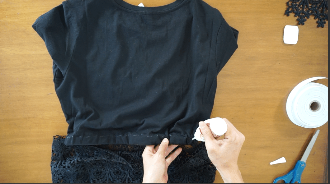 Use fabric glue to attach the lace trim to the bottom of the shirt and finish the diy lace peplum top.