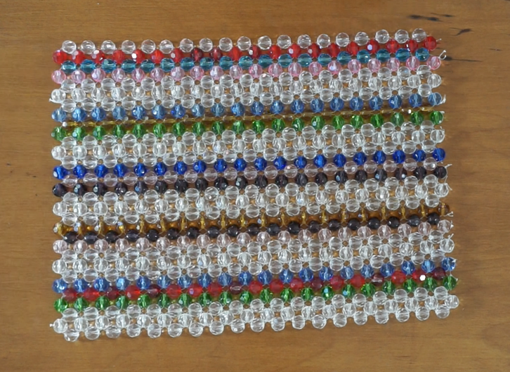 Free pattern for this beaded handbag. The handmade beaded bag uses rows of colored beads and rows of clear beads. The pattern includes instructions for handles and a flat bottom.