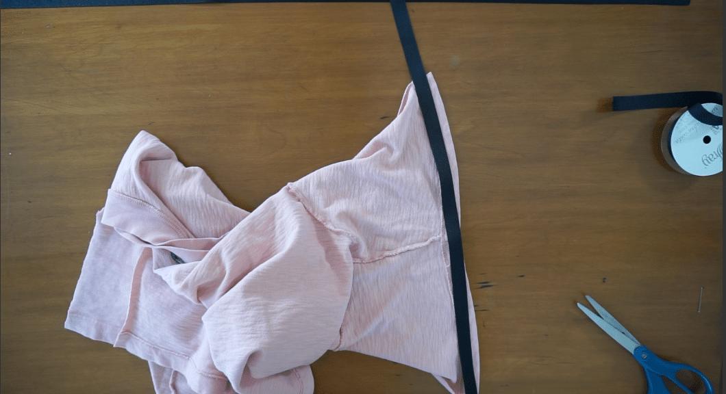 Lay the grosgrain strap on the hemline along the arm openin.