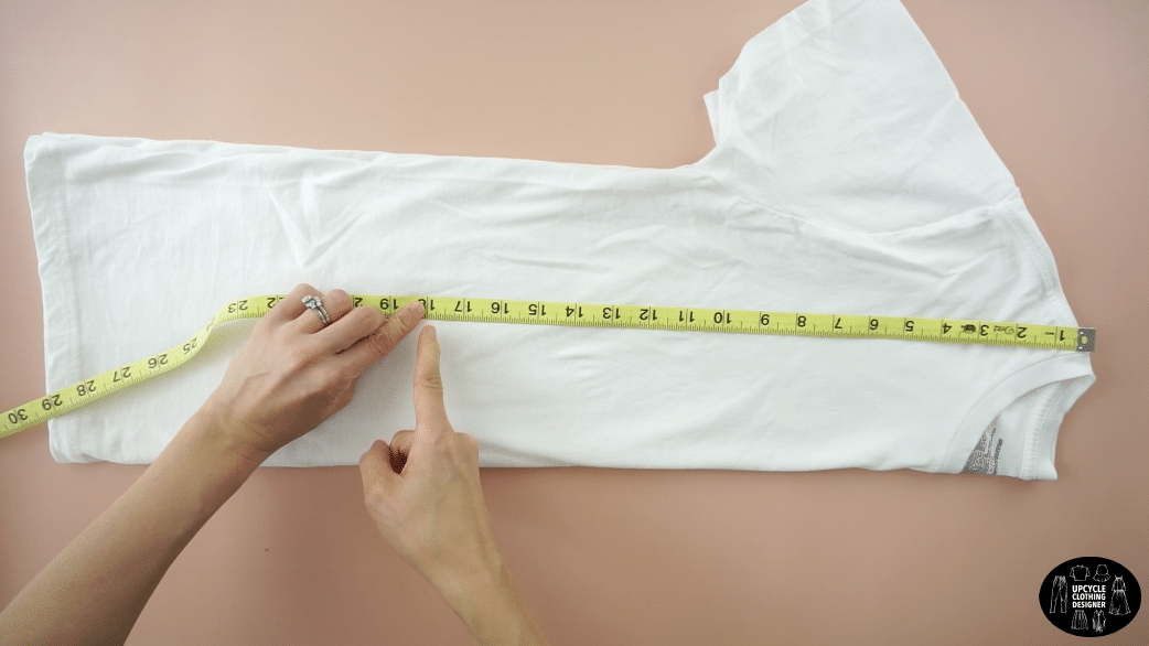 """Fold the t-shirt in half lengthwise. Mark 18"""" down from the high point on the shoulder."""