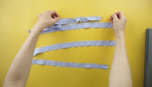 Use wide stitch width to topstitch along the center of the ruffle straps. Gently pull on the back thread to gather the fabric with bunching.