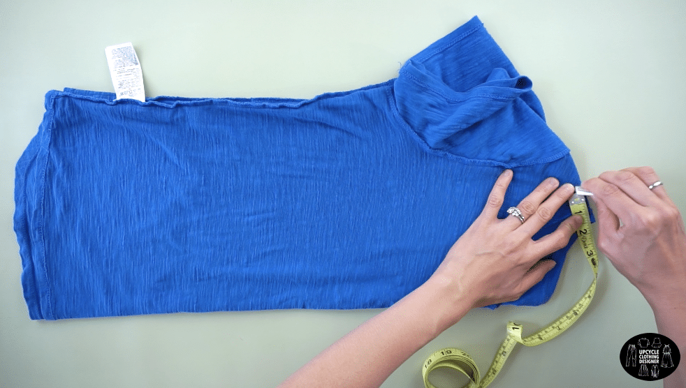 """Flip the tee inside out and fold it in half lengthwise. Measure 2"""" from the neckband on the shoulder seam."""
