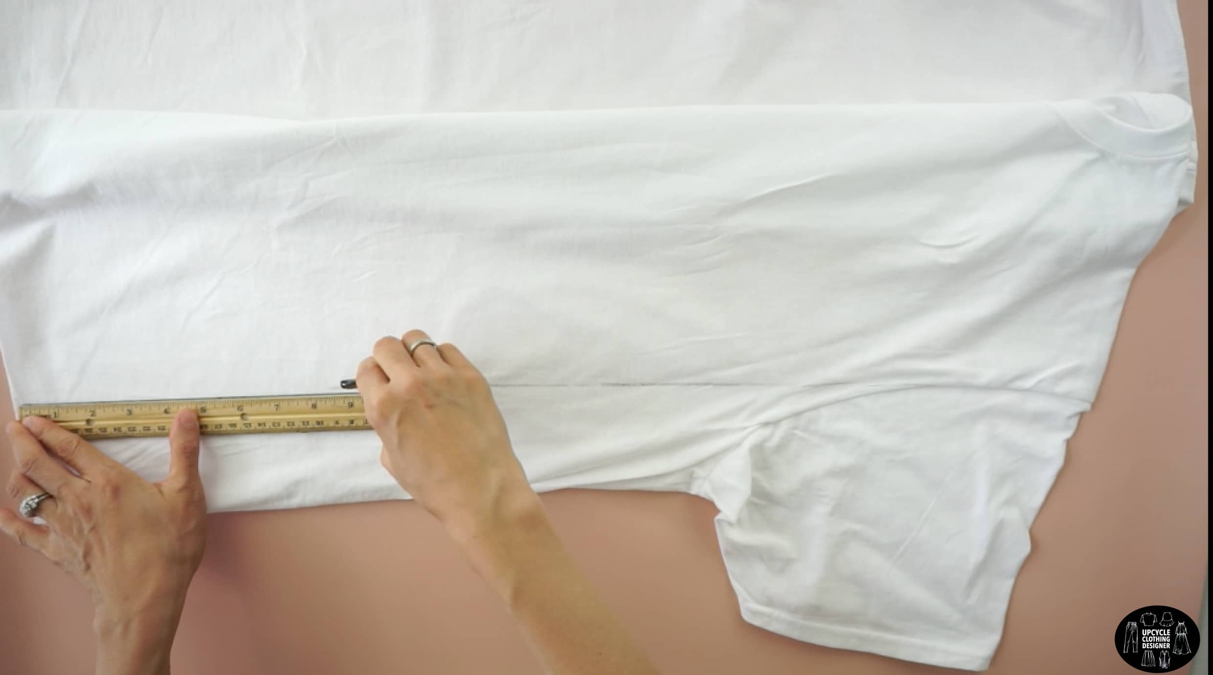 Lay the tee flat. Draw a straight line from the armhole opening to the hemline.