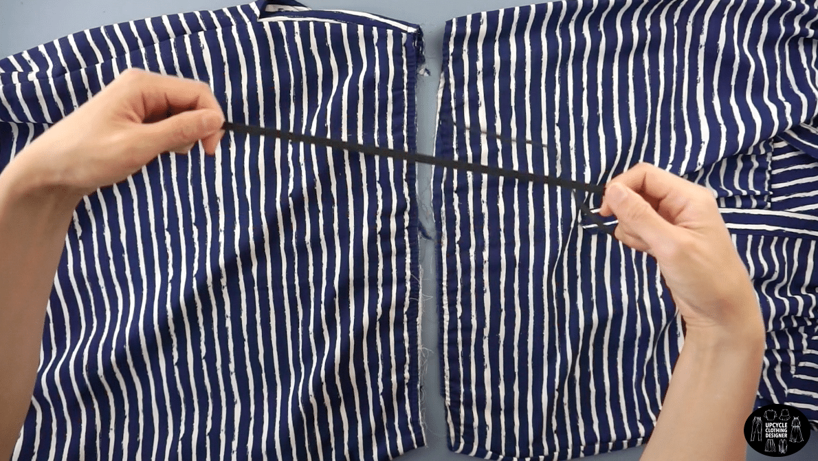 Cut across the waistband of the dress, and remove the elastic band.