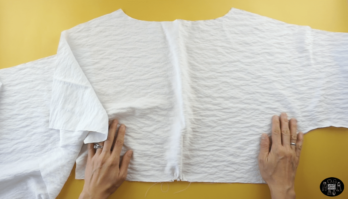 Pull on the back thread to create bunching with the fabric on the center back piece.