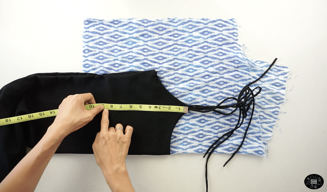 Fold the garment in half lengthwise, and pin along the edge. Fold a piece of fabric in half, and trace the side seam, high point shoulder, neckline and armhole opening.