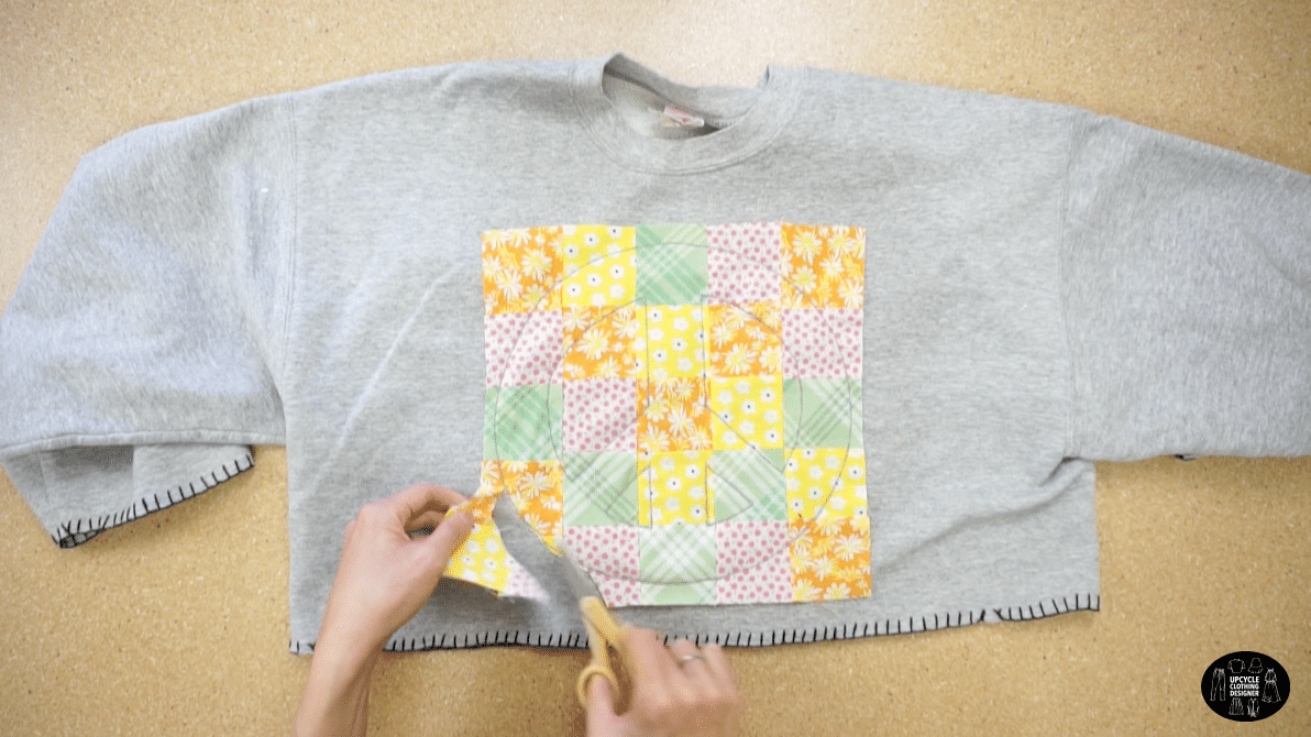 Cut off the ecess fabric to reveal the patchwork peace sign applique