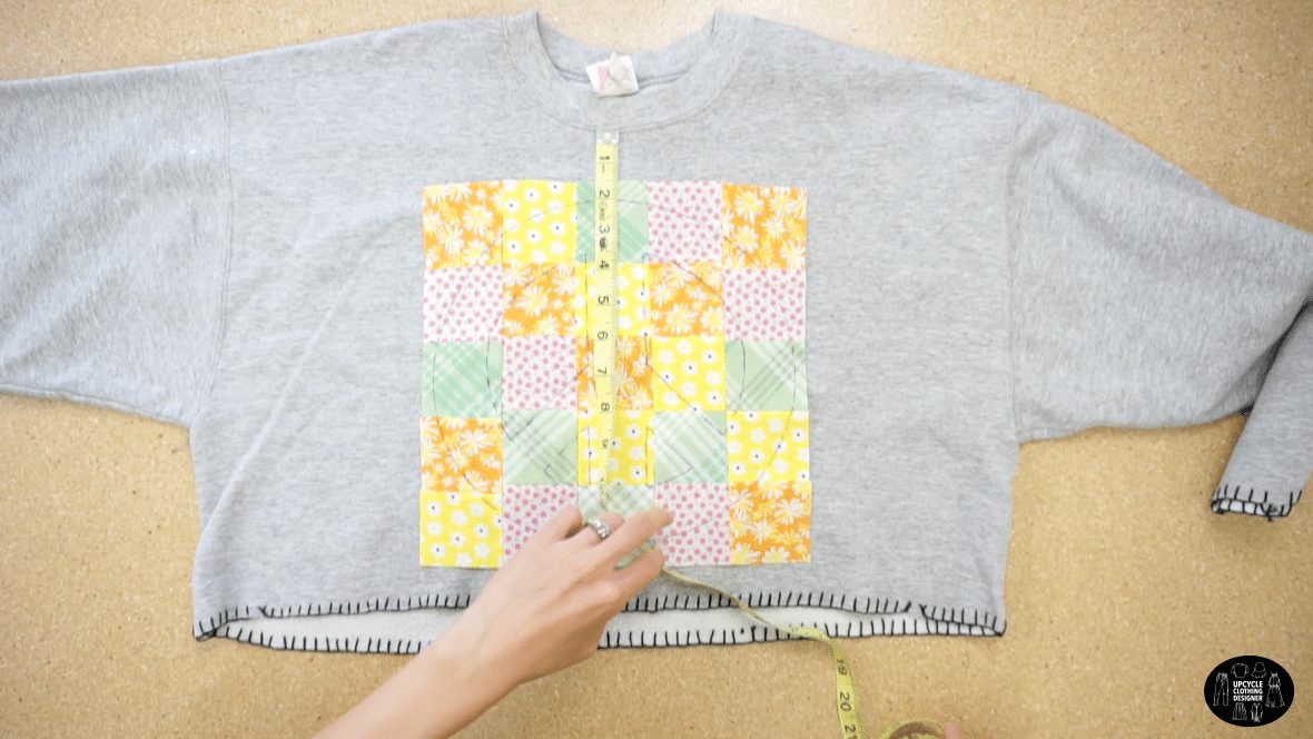 Align the patchwork fabric onto the front of the sweatshirt.