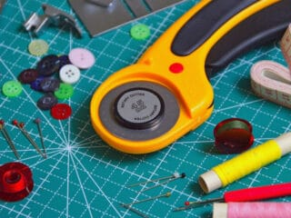 rotary cutter and fabric scissors on cutting board