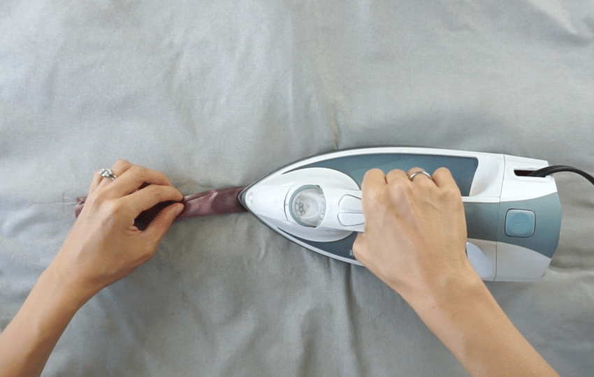Carefully rotate the seam to the side, and iron the strap flat.