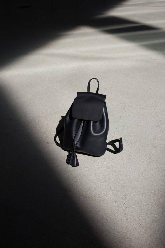 black leather backpack bag on the ground