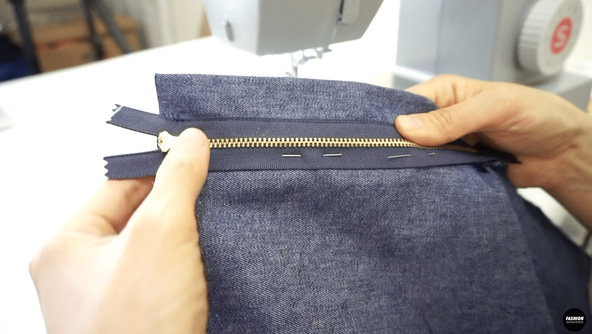 Stitch down the right side of the zip close to the zipper teeth and second row of stitching on the edge of the zipper tape.