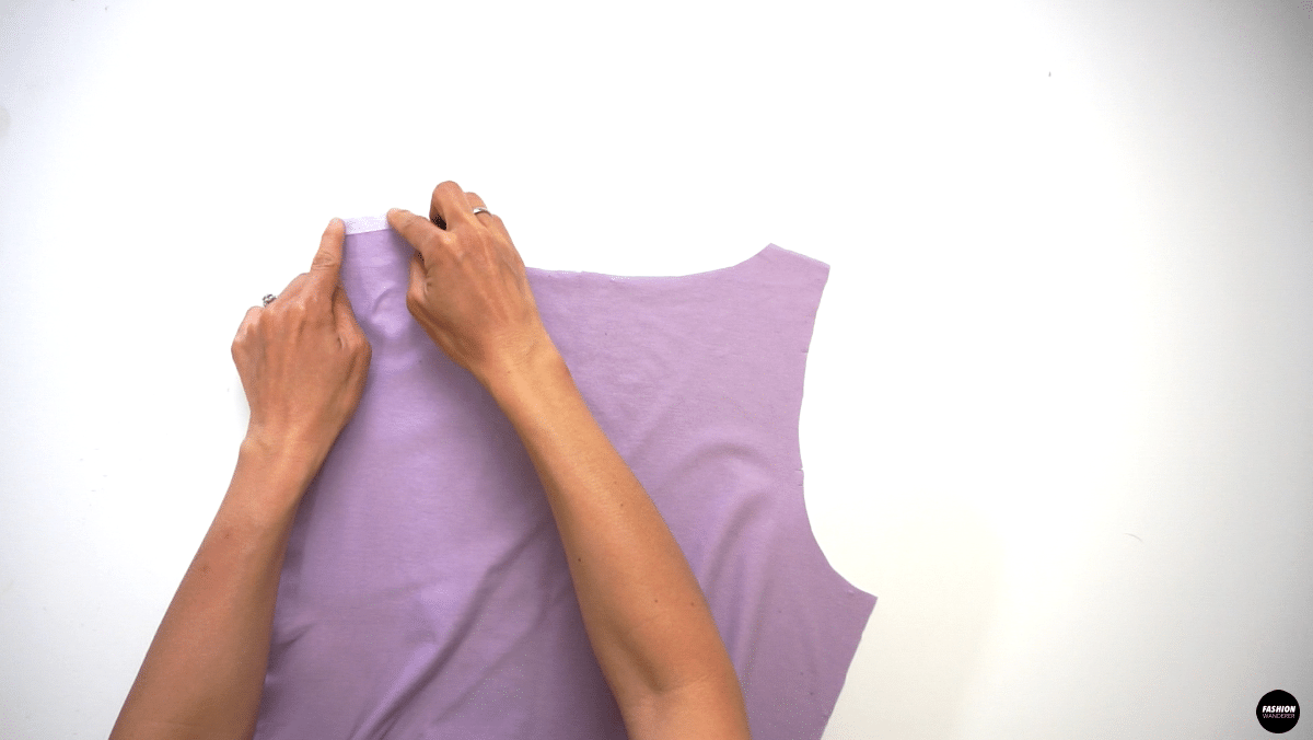 """Prepare 2 pieces of ⅜"""" width by 2"""" long fusible interfacing and lay on the wrong side of Back Top shoulder piece on both sides. Use hot steam iron to apply the interfacing on the garment."""