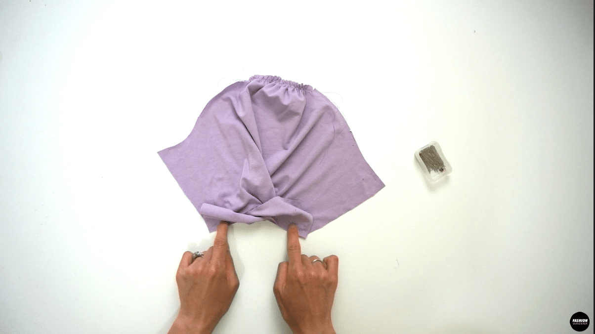 """Next, take the bottom leg piece on the front side of the sleeve and make two twists. Ensure the bottom leg of the sleeve matches the side of the sleeve and pin to secure. From side seam of the sleeve, ¼"""" straight stitch to zero close towards the twist. The closer you can get without sewing over the twist, the tighter the knot will become."""