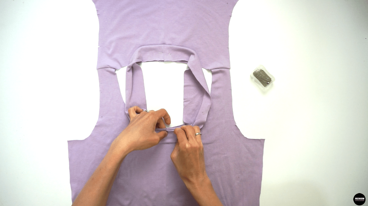 Fold the neckline wrong side facing each other and lay the bodice right side up. Match the center back seam of the neckband and center back notch of the bodice and pin. Also, match the center front notch of the neckband and bodice, then pin to secure.