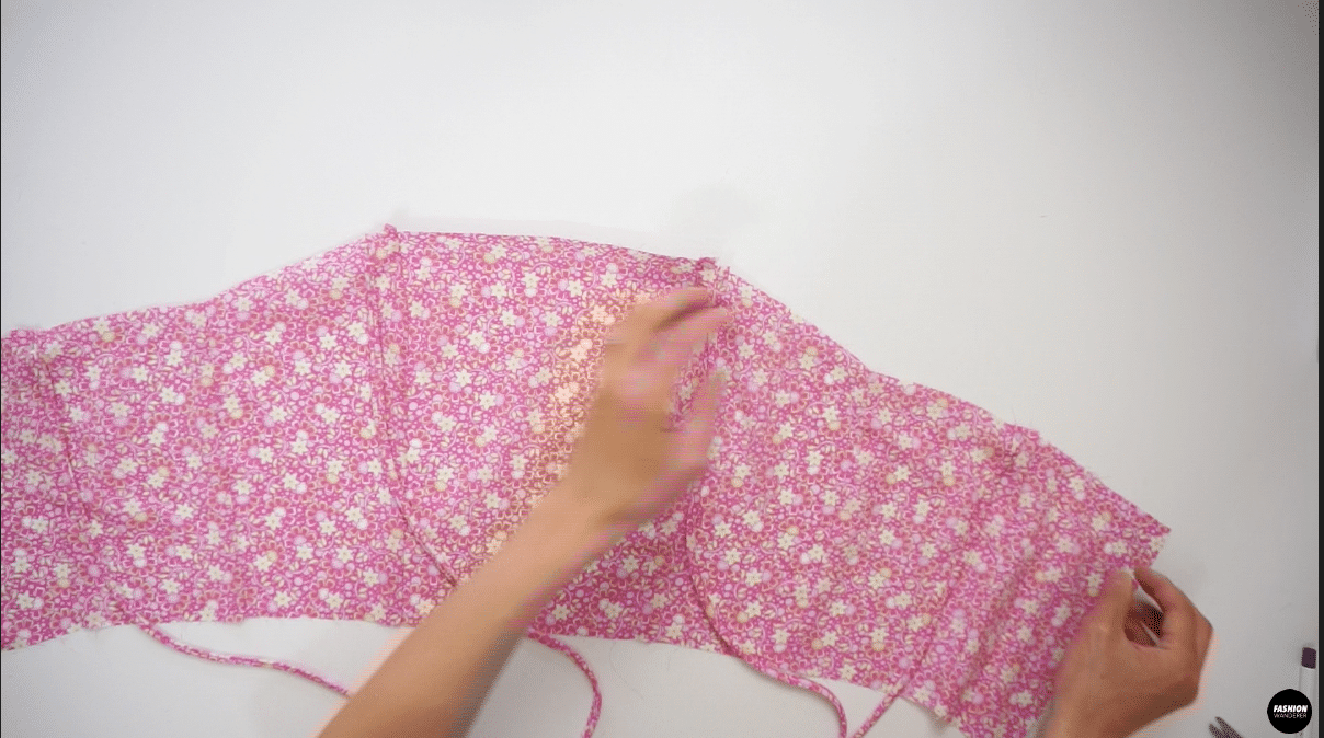 """Place the straps on the front and back notches on the right side of the Outer shell top and pin to secure. Sew ¼"""" width straight stitch back and forth to attach the strap to the bodice."""