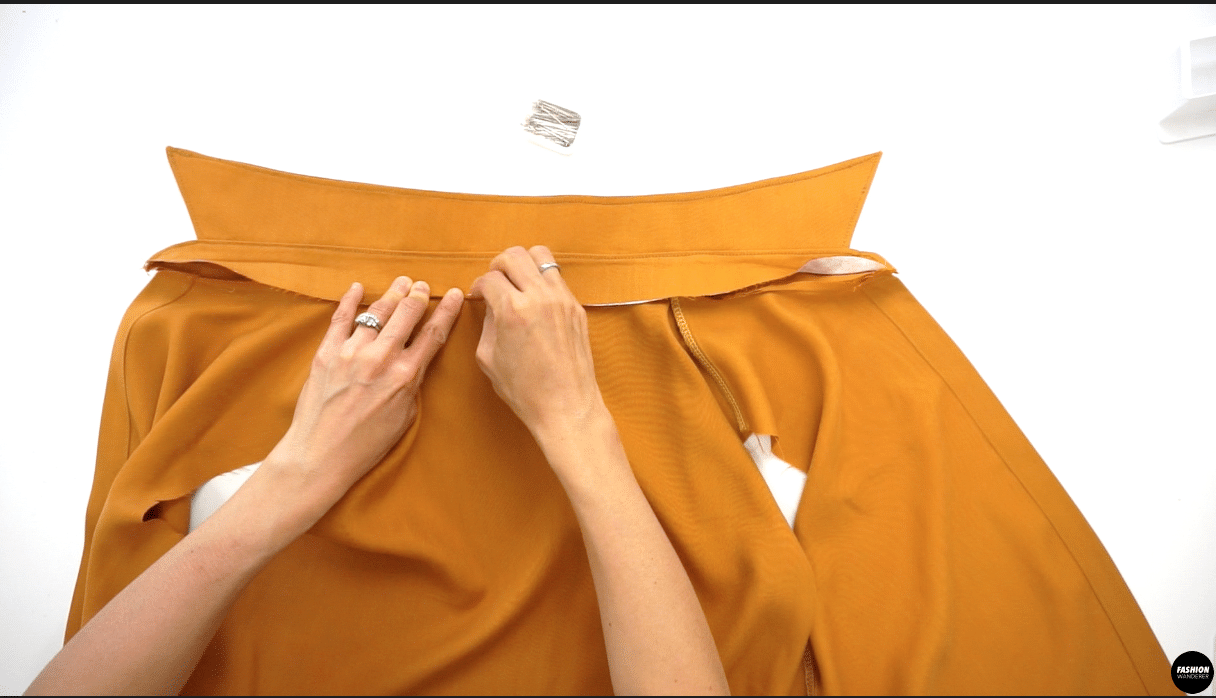 """Open the bodice and pin along the neckline with Collar Stand from one side to the other end. Sew ⅜"""" width along seam allowance. With Inner Collar Stand, fold ⅜"""" width and stitch in the ditch along the neckline seam."""