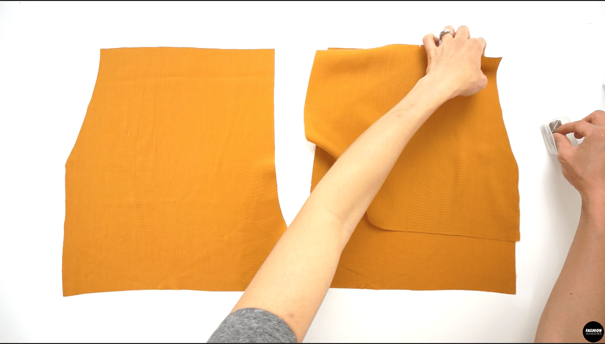 """Grab Shorts Pocket pattern piece and lay on top of wrong side of Front Shorts pieces, then pin along the curved pocket opening. Sew ⅜"""" width, then fold over along the seam and press."""
