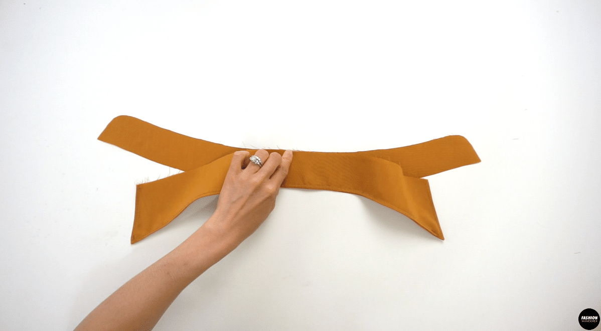 """Apply interfacing on Outer Collar Stand piece. Next, place right side of Inner Collar Stand upwards, and lay the collar on top. Match the center notch on both pieces and pin. Stay stitch the two pieces together with ¼"""" width to secure the position."""