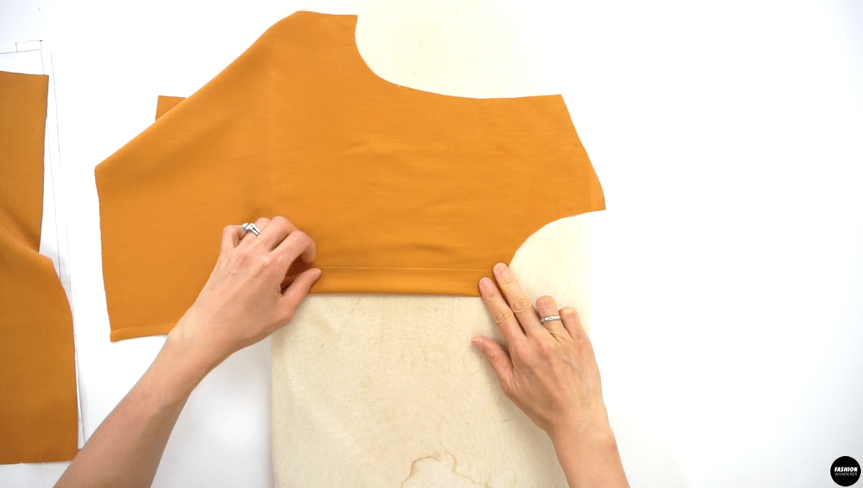 Lay the Front Right Side Top bodice wrong side up on the ironing board, fold along the first notch and press. Then, fold another time to reach to the next notch and press. Do the same on the Front Left Side Top bodice.