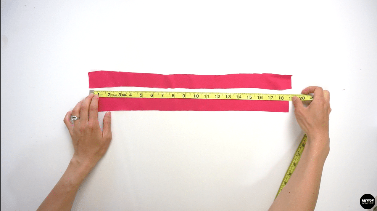 """Cut 2 pieces of 1½"""" width by 19"""" long fabric straps that are cut on bias. Fold the straps right side facing each other and sew straight ½"""" width. Trim the seam allowance so the finished edges will be ⅛"""" width remaining. Use a loop turner to flip the strap inside out and iron the strap flat."""