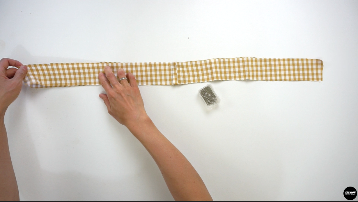 """Lay the right side of the Waistband facing each other and sew the top edge of the band lengthwise with ⅜"""" width seam allowance. Trim the corner on both pointy ends and flip the waistband inside out. Press with iron to shape the waistband."""