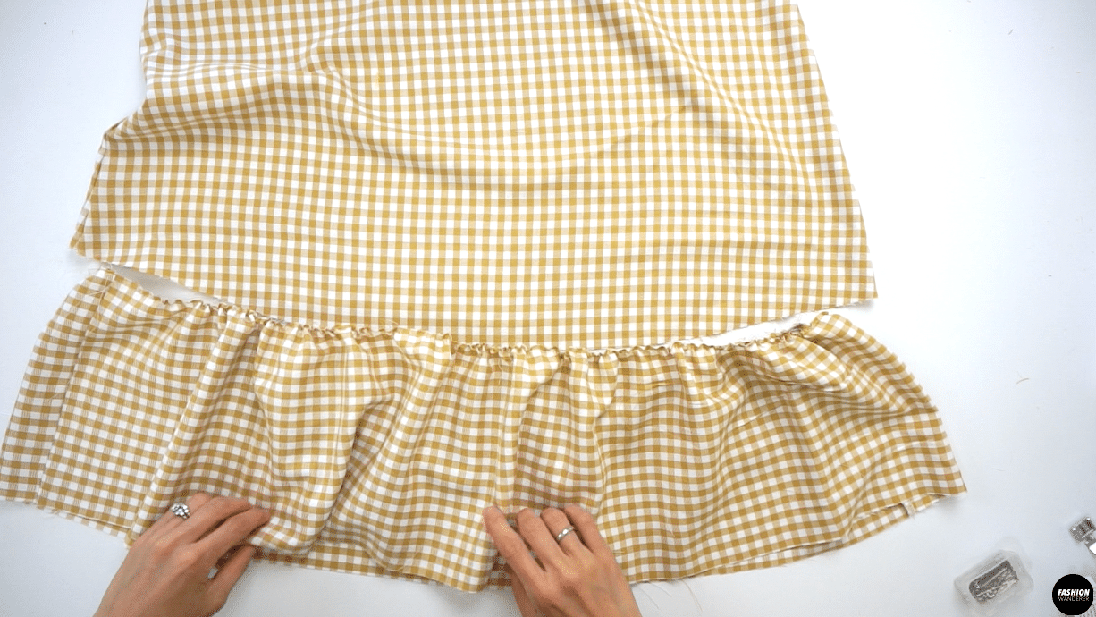 """Mark the center of the Front and Back Ruffle Hem Skirt piece and gently pull the back thread to start the gathering process. Match the notch and marked point, then pin each marked point and evenly distribute the gathering. Straight stitch ⅜"""" width and finish with overlock stitch. Lightly press on the gathering to make sure the seam allowance is facing down or toward the ruffle."""