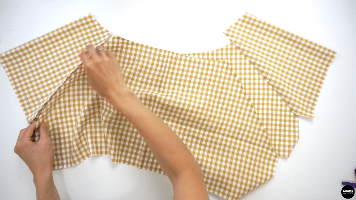 """Next, place the back side of the Sleeve facing the right side of the Back Top pattern, match the double notch in the middle and pin along the edge. Sew ⅜"""" seam allowance and finish with overlock stitch. Press the seam allowance toward the bodice."""