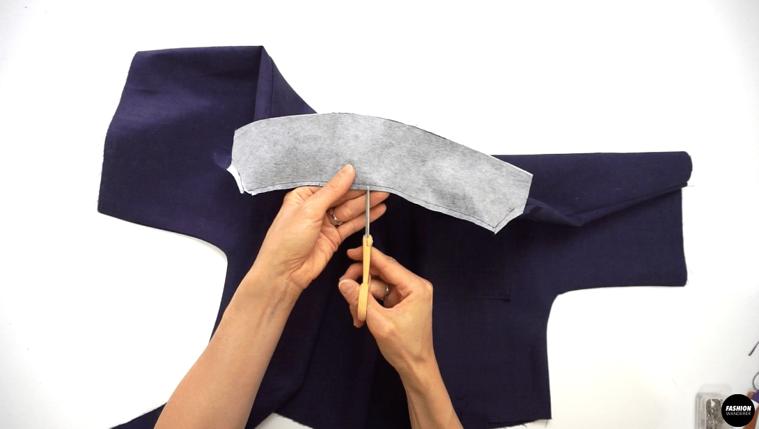 """Trim the seam allowance to ¼"""" width and slip the curved neckline to smooth out and release tension. Pin the short edge where the collar and the lapel are stitched together, up to where they are going to start breaking off. Insert the sewing needle where the stitch ended and sew the pinned edges right sides together to the breakpoint. Trim the seam allowance to ¼"""" width, also clip the corners and along the curve edges to release the tension. Press the seam open."""