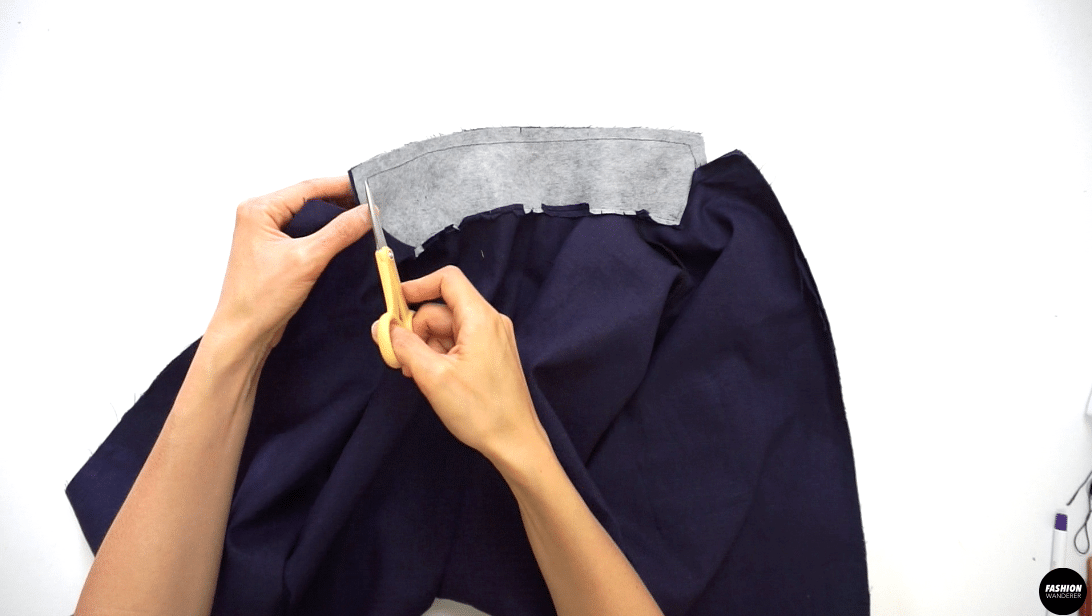 """Trim the seam allowance to ¼"""" width and clip the corners and notches around the collar. Turn the facing to the inside. Press and shape the point and edges with an iron."""