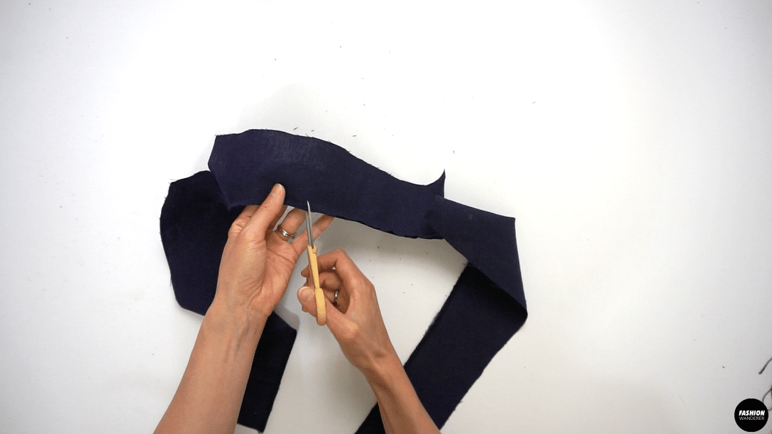 """Stitch the collar to the facing with ⅜"""" width seam allowance. Backstitch on both sides to secure the ends. Snip into seam allowance to release tension right to the point where the stitch starts and ends. Pin the short edge where the collar and the lapel are stitched together, up to where they are going to start breaking off. Insert the sewing needle where the stitch ended and sew the pinned edges right sides together to the breakpoint. Trim the seam allowance to ¼"""" width and also clip the corners and along the curved edges to release the tension. Press the seam open."""