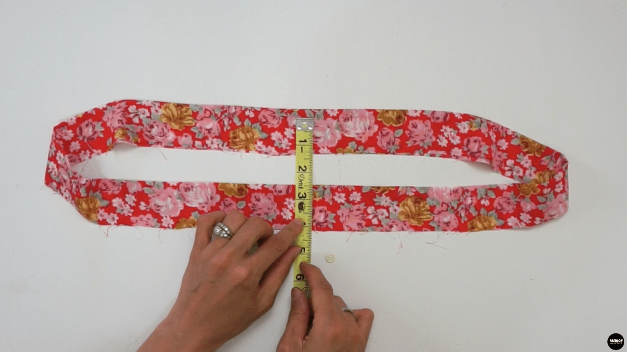"""In the Center Front of the waistband, measure ½"""" away from the folded edge and mark with water erasable pen. Then, measure ¼"""" away on both sides to indicate the opening for the drawstring tie. The opening of the tie is ⅜"""" long. Use buttonhole foot and a small button that is ⅜"""" in circumference to make the opening."""