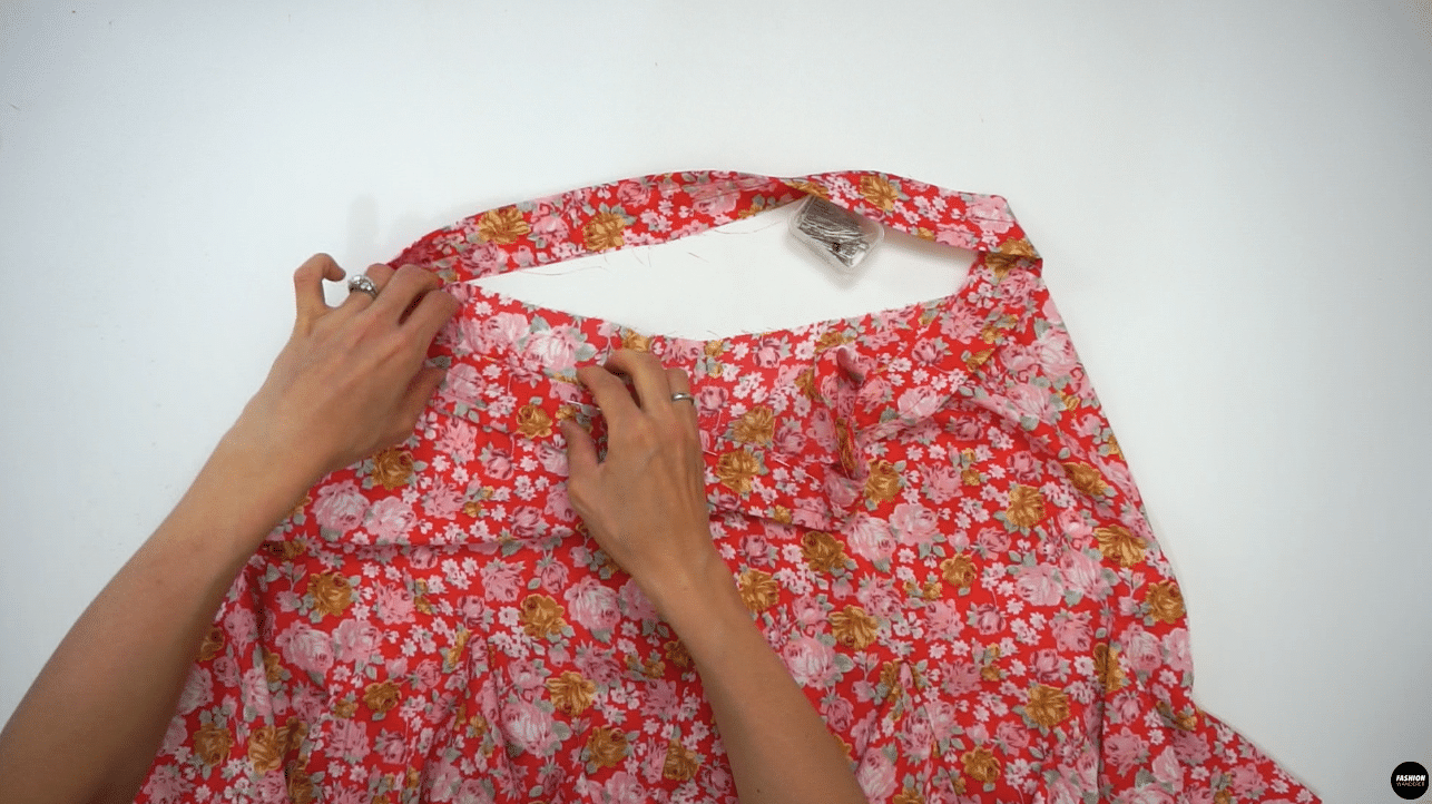 """Slide the waistband through the Skirt by matching Center Front, Center Back, and side seam notches. Pin and sew ⅜"""" width seam allowance around the waist opening, and finish with overlock stitch. Press the seam allowance toward the skirt."""