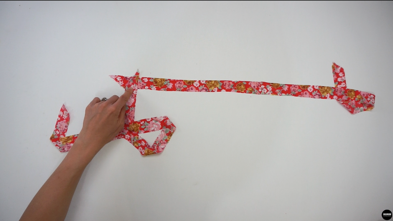 """Join the 2 pieces of 1"""" width and 30"""" long bias cut on one side and stitch diagonally to make it into one piece. Trim the edges and press the seam open. Fold the strap lengthwise facing right sides together and straight stitch ¼"""" width seam allowance. Use a loop turner to flip the strap inside out. Press gently to shape the drawstring tie."""