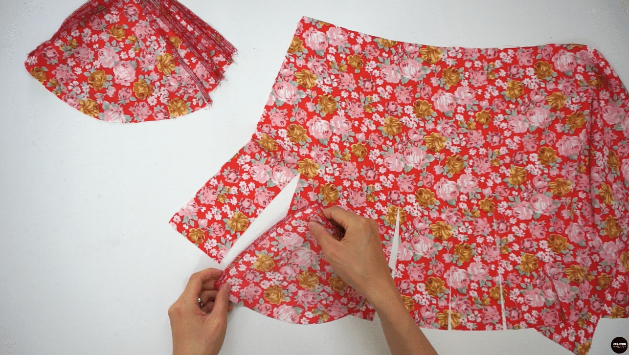 """To sew godet on the skirt, place Godet #1 pattern on the first cut line of the Front Skirt right side facing each other starting on the left side. Pin and sew ⅜"""" from the hem until a point where the seam allowance meets at a triangle. Match and pin the remaining right side of the godet to the opening and sew ⅜"""" straight stitch. Make sure to not backstitch near the point, and instead change the stitch length to 1 mm at the godet point. Then, change back to 2.5 stitch length and finish with backstitch along the hemline. Continue to insert Godet #1 pieces on all slits along the Front Skirt."""